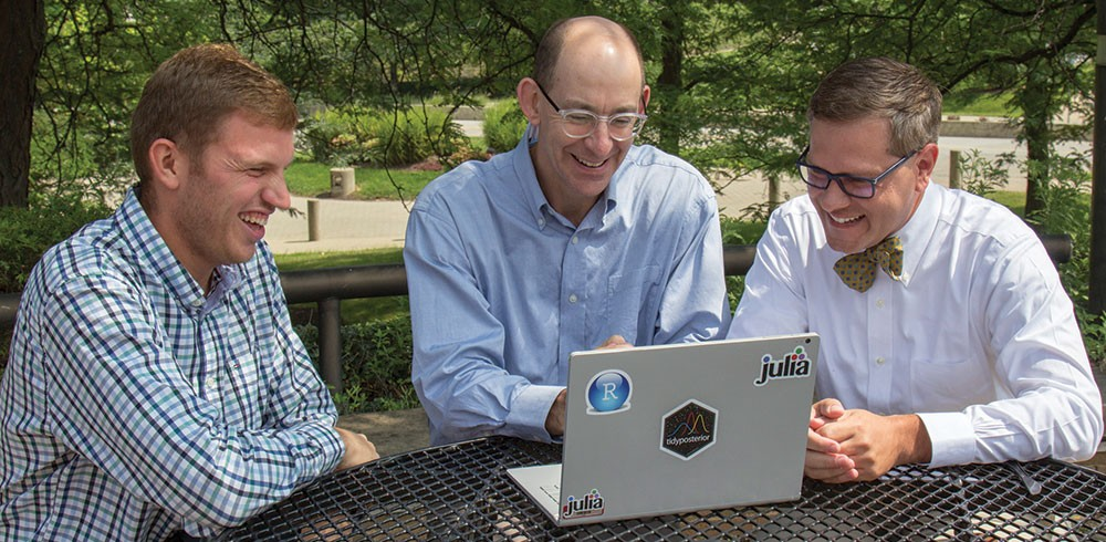 Left to right: Beau Sauley, Jeffrey Mills, and Jeffrey Strawn, seated at an outdoor table around a laptop