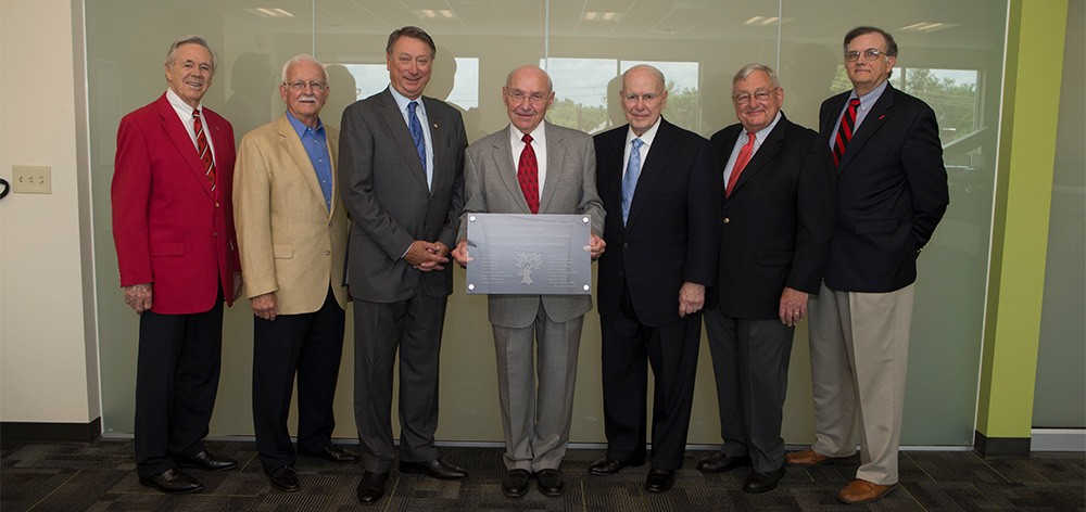 John Goering, center, holding a Hall of Fame plaque, flanked by local business leaders