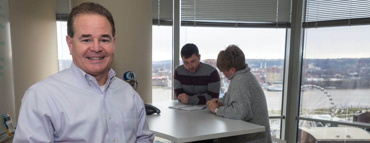 Larry Van Kirk of Valuation Research Company posing at his business with man and woman employees in the background, and view of city.