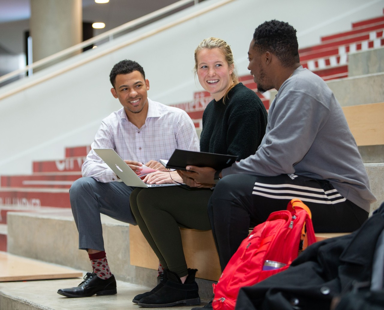 A female student wearing a black sweater sits between two male students on the steps of the Lindner atrium wearing casual clothing and talking