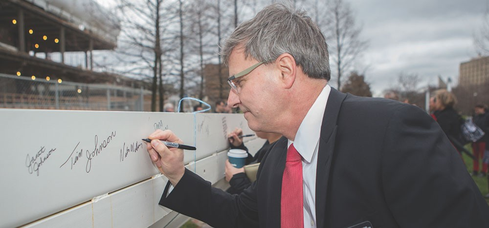 Interim Dean Nick Williams signing his name on the final steel beam for the new Carl H. Lindner College of Business building